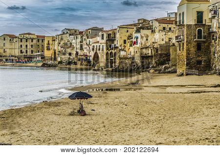 City of cefalu north of sicily sand sea and old constructions located at the foot of the beach island of sicily