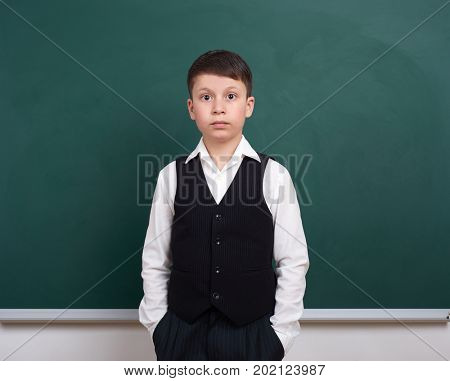 indifferent school boy portrait near green blank chalkboard background, dressed in classic suit, one pupil, education concept