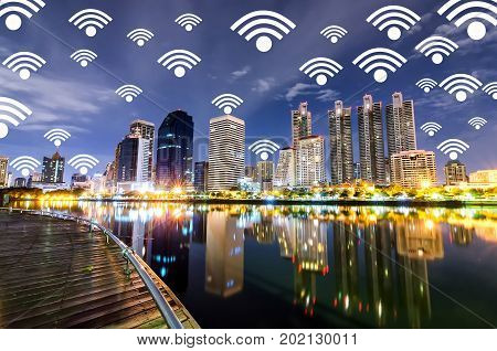 Internet network connection and telecommunication. City lifestyle people use digital data transfer social network via wifi connection. Wifi Icon on Cityscape in twilight as Background.