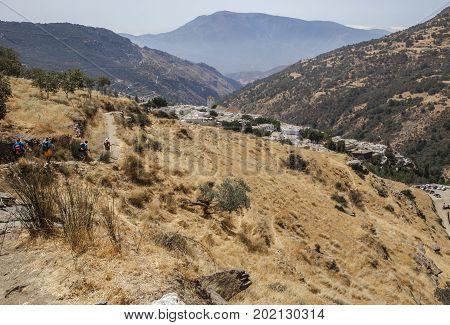 Hiking group descending along Poqueira Gorge to Capileira. Las Alpujarras Region Granada Spain