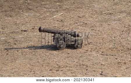 A small wooden cossack cannon on wheels standing in the yard photo.