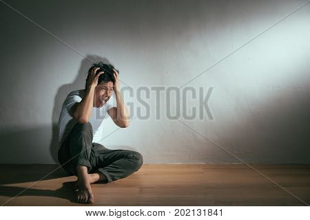 Collapsed Man Sitting On Wood Floor Hand Hold Head