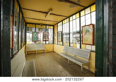 GHENT BELGIUM - JUNE 22 2016: Detail picture of an empty yellow waiting room in Ghent Sint Pieters Train Station with green iron columns three white wooden seats and vertical windows. Ghent Belgium.