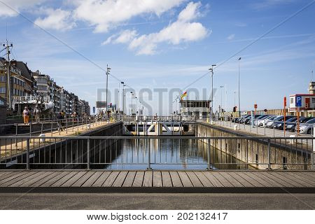 OOSTENDE BELGIUM - JUNE 22 2016: Picture of the Oostende pier with a wooden deck a floodgate with refletion and a parking lot in a sunny day with clouds. Oostende Belgium.