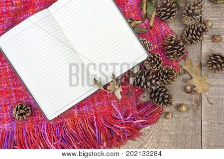 Open Journal With Blank Lined Paper On Top Of Autumn Knitted Throw, Rustic Wooden Surface With Acorn