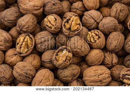 A table filled with walnuts for sale. Some are cracked to show the interior nut.