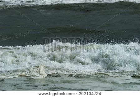 Closeup of crashing waves, surf, and sea spray during ominous tropical storm in Florida.