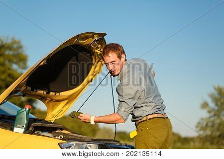 The man checks the oil level in the engine of the car. Trouble on the road. Repair on the road.