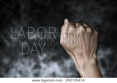 closeup of the raised fist of a young man against a gradient dark gray background and the text labor day