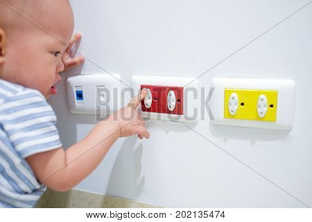 Curious Asian toddler baby boy child play with electric plug. Try to insert it into socket Baby hand reach for electrical outlet covered with red safety plugs (child safety concept) - Selective focus