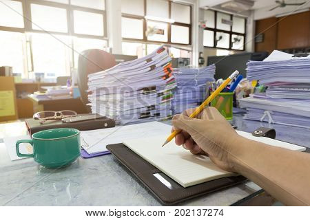 Business And Finance Concept Of Office Working, Businessman Writing On A Notebook With Pile Of Unfin
