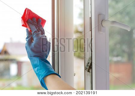 Female Hand In Blue Rubber Glove Wipes Glass. Washes White Plastic Window. Closeup
