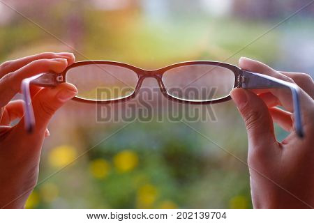 Eyes Through The Glasses. Points In The Girl's Hands. The Blurred Image In The Glass. Closeup