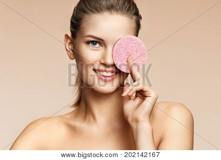 Smiling girl cleaning face with exfoliating sponge. Portrait of funny young girl on beige background. Youth and skin care concept