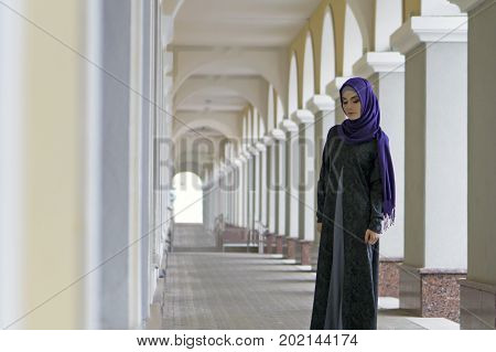 girl of Middle Eastern appearance in Muslim clothes standing in the city gallery Ufa