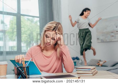 young bored woman studying while her friend dancing on bed