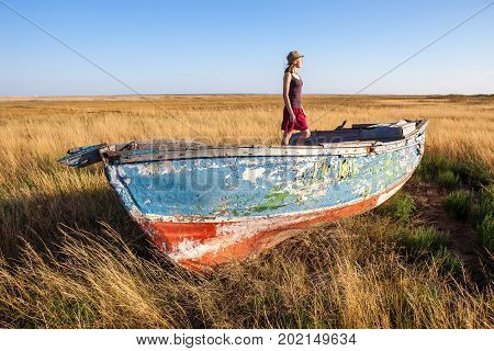 Young girl seaman floats on a boat in the field at sunset on a warm summer evening. at sunset. the dream of travel