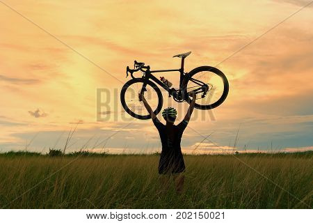 Silhouette of a cyclist with a raised bike in the sun