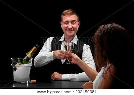 Close-up picture of a handsome barman and a beautiful girl with long curly hair flirting behind the bar counter on a saturated black background. A glamorous girl drinking a champagne. Nightclub.