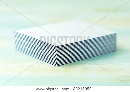 A stack of blank layered business cards with painted edges, on a teal background, with a shallow depth of field. Selective focus photo, place for text.