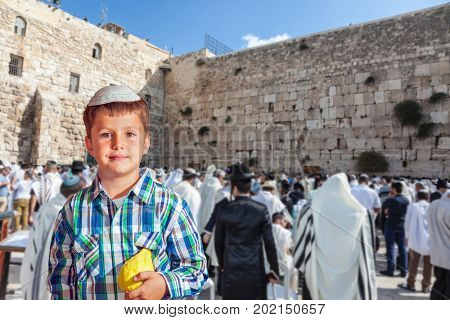 Sukkot at the Western Wall of Temple in Jerusalem. Charming seven year old boy in white festive skullcap with etrog