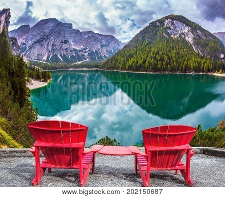 The concept of walking and eco-tourism. Two comfortable red deck chairs on the shore of the lake. Water reflects the surrounding mountains