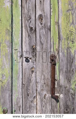 Old rust hinge in green wooden door