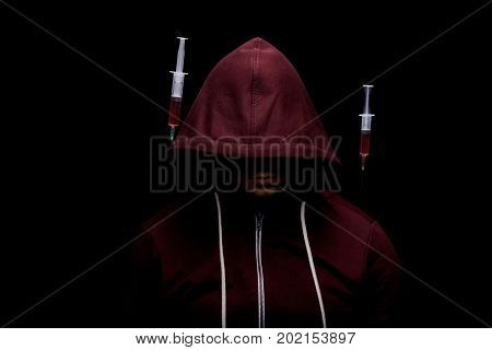An addict male with syringes full of red liquid drugs near him on a saturated black background. A hopeless drug addict is going through addiction crisis. Depression, abuse, fear concept.