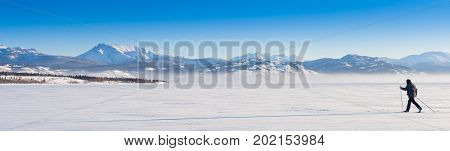 Person skiing on cross-country skis casts long shadow on untouched powder snow enjoying freedom of wide open wilderness landscape