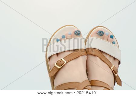 Female Feet In Sandals With A Manicure On A Light Background. Close-up