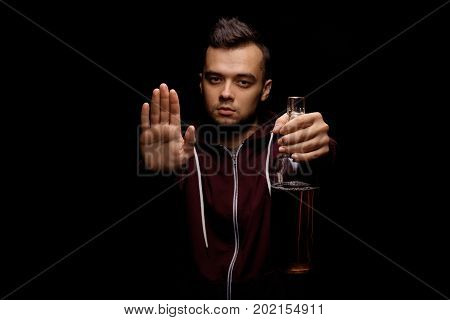The man refused to drink alcohol and showed a sign of the stop sign on a saturated black background. A young male saying no more to alcohol with his body language. Copy space.