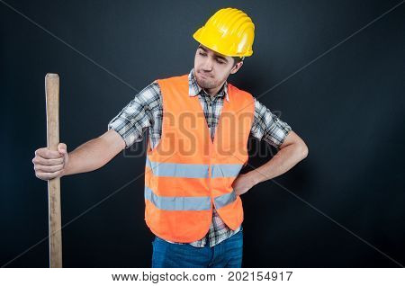 Constructor Wearing Equipment Looking At Digging Hoe