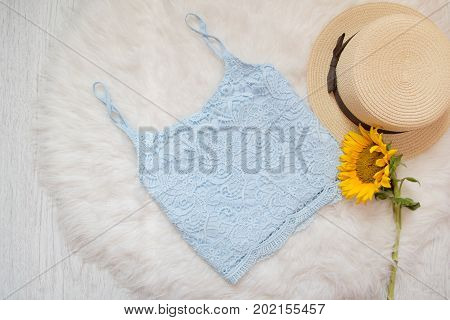 Blue Lace Top, Straw Hat And Sunflower. On White Fur, Top View