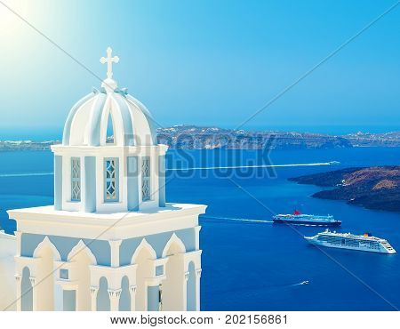 Blue dome of a famous church in Santorini with view on the caldera