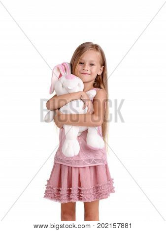A delightful little girl is embracing big soft rabbit toy, isolated on a white background. A happiness kid with long blond hair in a pink dress hugging a plaything. Childhood and toys concept.