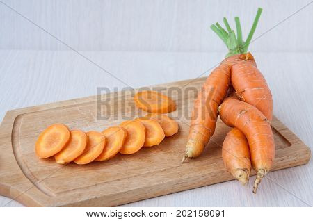 Raw Carrots Whole And Sliced On A Wooden Board
