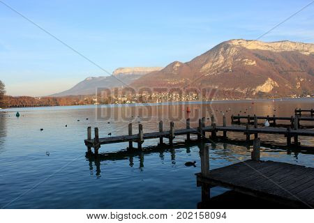 Beautiful view of the Annecy Lake in French Alps, a spring day with snow in the mountains and with boats in the foreground. Annecy. Haute Savoie. French Alps. France.