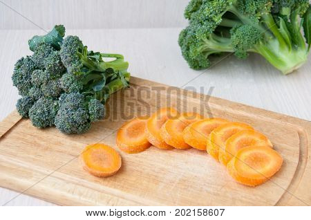 Raw Carrot Sliced And Broccoli On A Wooden Board