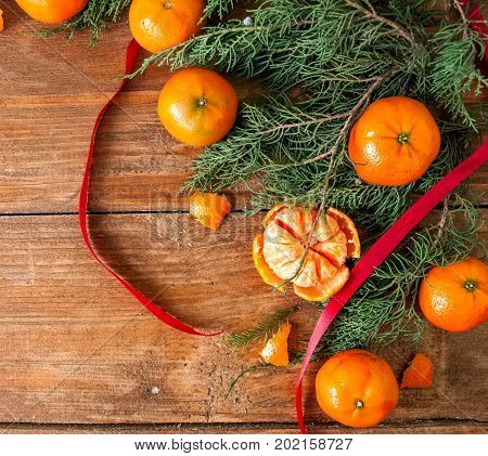 Tangerines (mandarins) with christmas tree branches and red rope on wooden background. Copy space.
