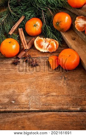 Tangerines (mandarins) with christmas tree branches with spices on wooden background. Copy space.