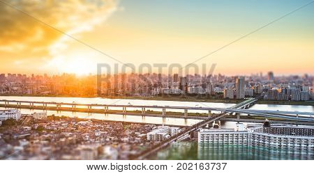 Business and culture concept - panoramic modern city skyline bird eye aerial view under dramatic sunset glow and beautiful cloudy sky in Tokyo Japan. Miniature Tilt-shift effect