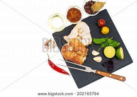 Plate with chunks of fresh chicken and seasonings . Studio Photo