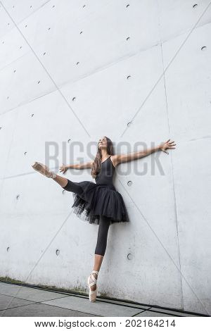 Sensual ballerina with closed eyes stands on the left toe and leans on the textured concrete wall outdoors. Her right leg and arms are outstretched to the sides. Girl wears a dance wear and pointes.