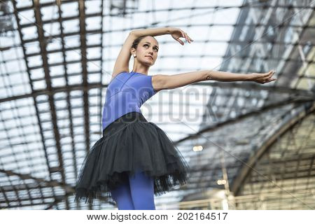 Amazing ballerina is posing on the railway station. She outstretches her arms to the side and looks upward. Girl wears a blue dance wear with a black tutu. Closeup. Horizontal.