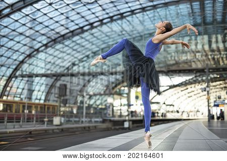 Incredible ballerina is posing on the railway station. She stands on the right toe with tilted left leg and pulls her hands backward. Girl wears a blue dance wear with a black tutu and light pointes.