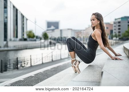 Cool dancer leans on the hands and toes while holding her pelvis in the air on the stairs on the background of the river embankment in the city. She wears a black top with leggings and pointes.