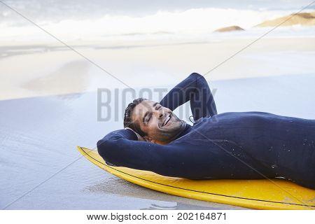 Relaxing surf dude on board on beach portrait