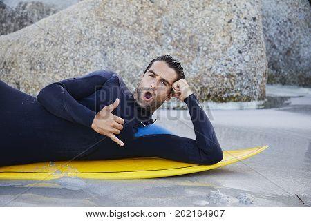 Surfer dude in wetsuit gesturing on board portrait