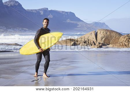 super cool Surfer dude carrying board on beach