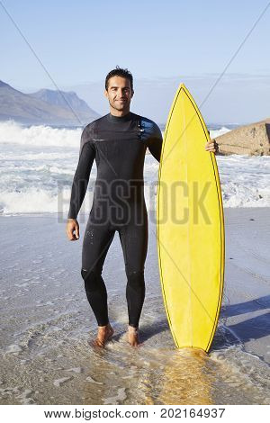 Surfer dude in wetsuit standing with board on beach